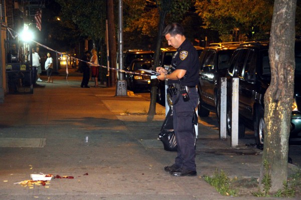 A police investigator takes notes after a shooting left three wounded on Briggs Avenue on July 21. (Photo by David Greene)