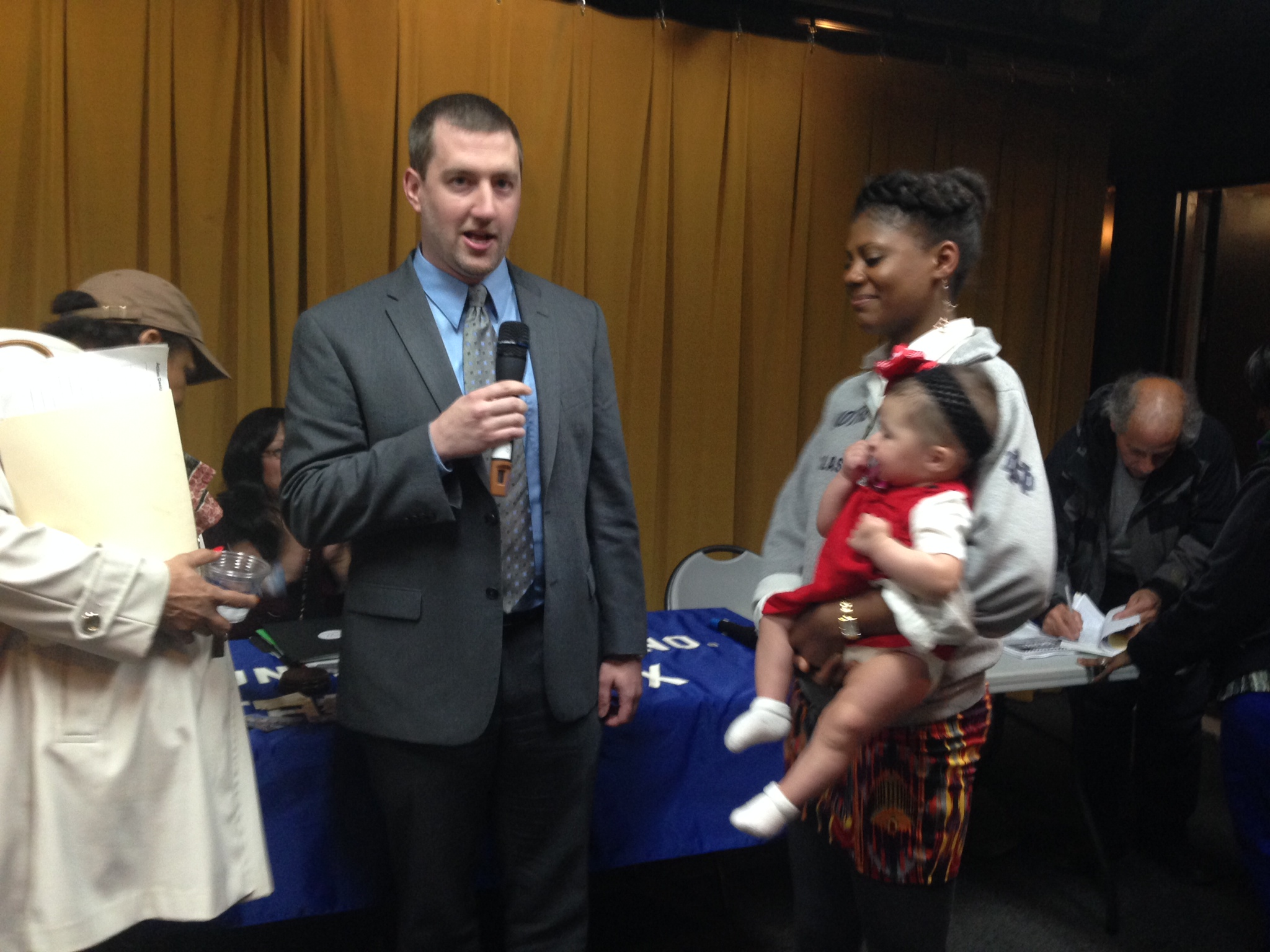 Dustin Engelken accepts the job as district manager of Community Board 7, standing alongside his wife and baby girl. Photo by Justin McCallum