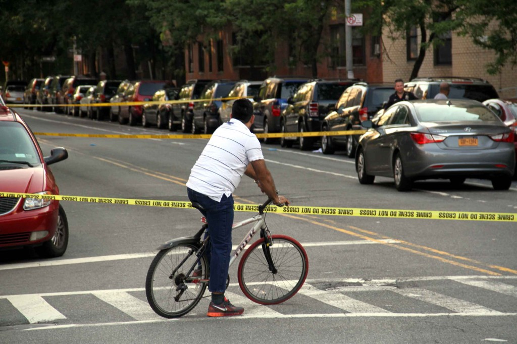 A bicycle rider stops to watch a police crime-scene at University Avenue and West 197 Street.--Photo by David Greene