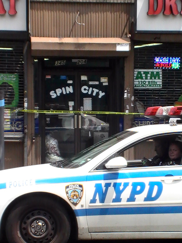 Police outside of the Spin City Laundromat on East 204 Street, where police arrested three men who broke into the store's ATM machine.--Photo by David Greene