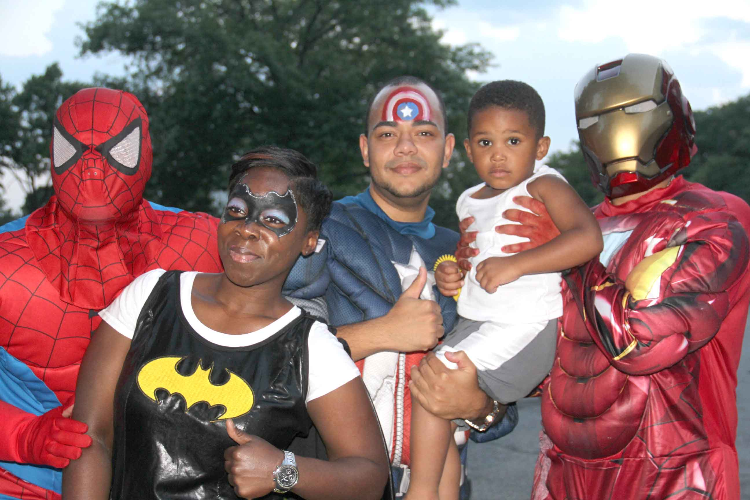 Police officers decked in superhero outfits join kids at National Night Out Against Crime. Photo by David Greene