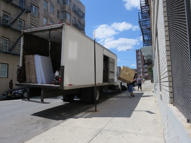 MOVERS HAUL OUT appliances and furniture intended for several apartments at 319 E. 197th St. purported to have been set aside for homeless residents. Photo by David Cruz