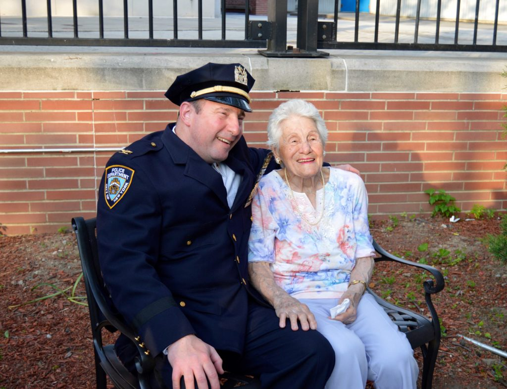 MARY VALLATI (RIGHT), shares a moment with former 52nd Precinct commanding officer, a guest at a bench dedication ceremony for Vallati on May 26. Photo by Daniela Beasley