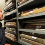 ANGEL HERNANDEZ, THE Bronx County Historical Society's director of programs and external relations, looks at the collection of physical atlases held at the Norwood office.  Photo by David Cruz