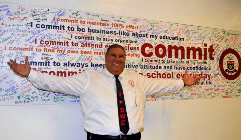 SANTIAGO TAVERAS, PRINCIPAL of DeWitt Clinton High School, stands in front of banner filled with signatures of students committed to graduate high school in four years. Monroe College helped introduce the initiative at the school. Photo courtesy Monroe College