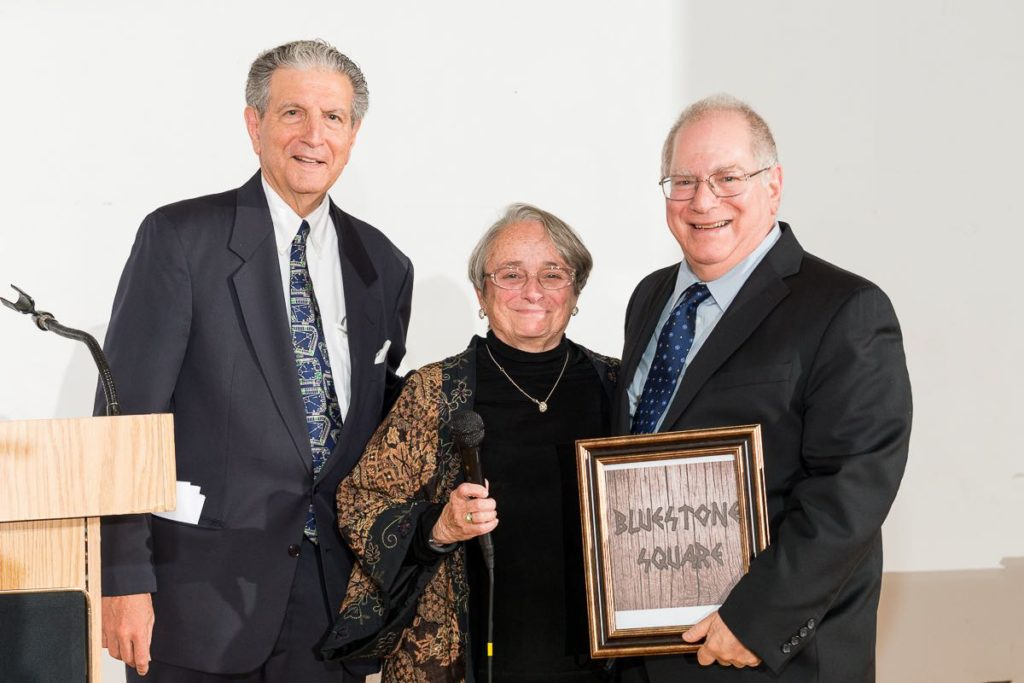 (L-R) BRUCE SCHLECTER, Mosholu Montefiore Community Center treasurer; and Natly Esnard, co-chair of MMCC's Board of Directors, pose with Donald Bluestone, the Center's longtime executive director, at a ceremony honoring him on Oct. 20.  Photo courtesy MMCC